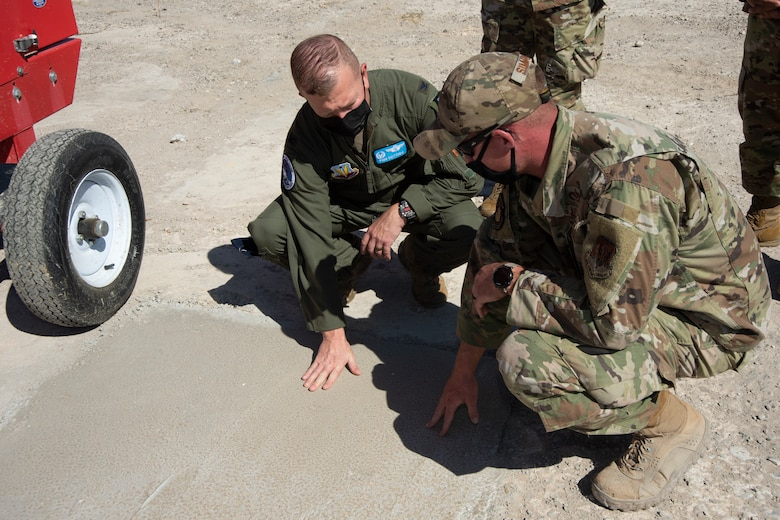 An Airman shows how effective rapidset concrete is for ground damage recovery to the Colonel.