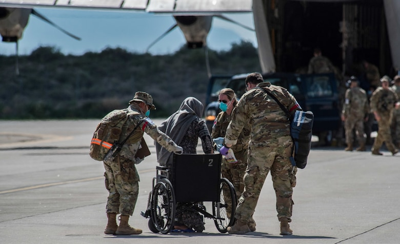 Airmen from Task Force-Holloman assist an Afghan evacuee into a wheelchair on the ramp at Holloman Air Force Base, New Mexico, Aug. 31, 2021. The Department of Defense, through U.S. Northern Command, and in support of the Department of State and Department of Homeland Security, is providing transportation, temporary housing, medical screening, and general support for up to 50,000 Afghan evacuees at suitable facilities, in permanent or temporary structures, as quickly as possible. This initiative provides Afghan evacuees essential support at secure locations outside Afghanistan. (U.S. Air Force photo by Staff Sgt. Kenneth Boyton)