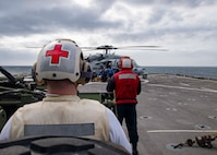"""210226-N-NQ285-1210 ATLANTIC OCEAN (Feb. 26, 2021) Hospital Corpsman 1st Class Eric Lewis, left, from Pensacola, Florida and assigned to the Harpers Ferry-class dock landing ship USS Carter Hall (LSD 50), provides medical coverage during a personnel transfer in an MH-60S Sea Hawk helicopter, assigned to the """"Chargers"""" of Helicopter Sea Combat Squadron (HSC) 26, on the ship's flight deck, Feb. 26, 2021. Carter Hall is conducting training with Amphibious Squadron 4 and the 24th Marine Expeditionary Unit (24th MEU) as part of the Iwo Jima Amphibious Ready Group. (U.S. Navy photo by Mass Communication Specialist Seaman Sawyer Connally)"""