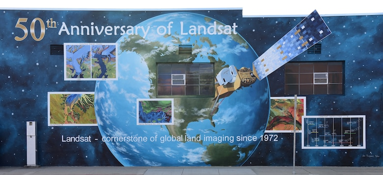 Ann Thompson, City of Lompoc Mural Society curator, started painting the earth of the mural on Ocean Blvd and I street June 27, 2021 in Lompoc, California. The mural will be implementing the history of the progression of the Landsat satellites numbers one through eight. (U.S. Space Force photo by Airman First Class Tiarra Sibley)