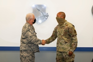 Civil Air Patrol Chief of Chaplains emeritus Chaplain (Col.) John Murdoch shakes hands with Col. Randel Gordon, 412th Test Wing Vice Commander, signifying a partnership between the Wing and CAP to augment the Wing's chaplain staff at Edwards Air Force Base, California, Sept. 10. (Air Force photo by Katherine Franco)