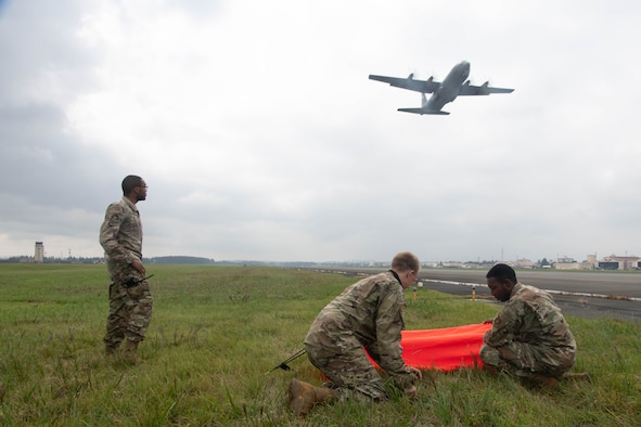 Airmen looking into a supply box