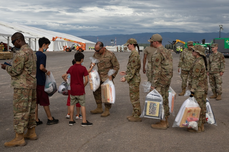 Airmen hand out basic essentials to arriving Afghan personnel as part of Operation Allies Welcome on Holloman Airforce Base Sept. 2, 2021. The Department of Defense, in support of the Depart of State, is providing transportation and temporary housing in support of Operation Allies Welcome. This initiative follows through on America's commitment to Afghan citizens who have helped the United States, and provides them essential support at secure locations outside Afghanistan. (U.S. Army photo by Spc. Nicholas Goodman)