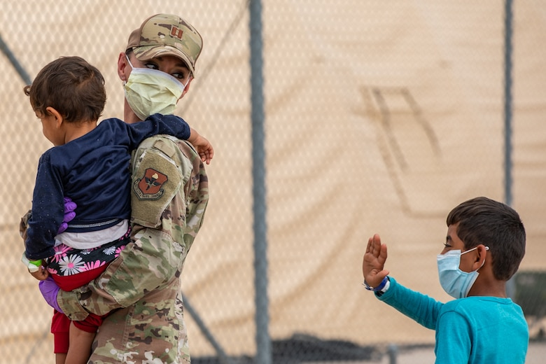 An Airman attached to Task Force-Holloman aids Afghan children as they arrive to Holloman Air Force Base, New Mexico, Sept. 2, 2021. The Department of Defense, through U.S. Northern Command, and in support of the Department of State and Department of Homeland Security, is providing transportation, temporary housing, medical screening, and general support for up to 50,000 Afghan evacuees at suitable facilities, in permanent or temporary structures, as quickly as possible. This initiative provides Afghan evacuees essential support at secure locations outside Afghanistan. (U.S. Army photo by Pfc. Anthony X. Sanchez)
