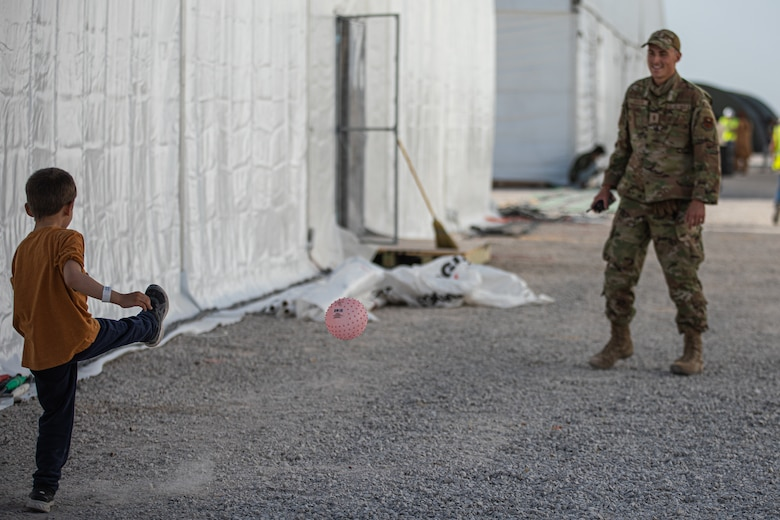 An Airman attached to Task Force-Holloman plays with an Afghan evacuee at Aman Omid Village on Holloman Air Force Base, New Mexico, Sept. 5, 2021. The Department of Defense, through U.S. Northern Command, and in support of the Department of State and Department of Homeland Security, is providing transportation, temporary housing, medical screening, and general support for at least 50,000 Afghan evacuees at suitable facilities, in permanent or temporary structures, as quickly as possible. This initiative provides Afghan evacuees essential support at secure locations outside Afghanistan. (U.S. Army photo by Pfc. Anthony Sanchez)