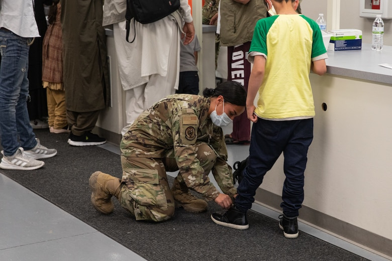 A Task Force-Holloman Airman ties an Afghan child's shoes as he waits to in process at Holloman Air Force Base, New Mexico, Sept. 2, 2021. The Department of Defense, through U.S. Northern Command, and in support of the Department of Homeland Security, is providing transportation, temporary housing, medical screening, and general support for at least 50,000 Afghan evacuees at suitable facilities, in permanent or temporary structures, as quickly as possible. This initiative provides Afghan personnel essential support at secure locations outside Afghanistan. (U.S. Army photo by Spc. Nicholas Goodman)