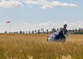 Airman standing in field packing parachute