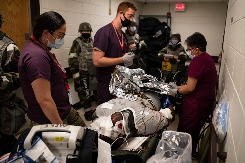 Members of the 51st Medical Group treat a patient with multiple mock injuries during a mass casualty training event
