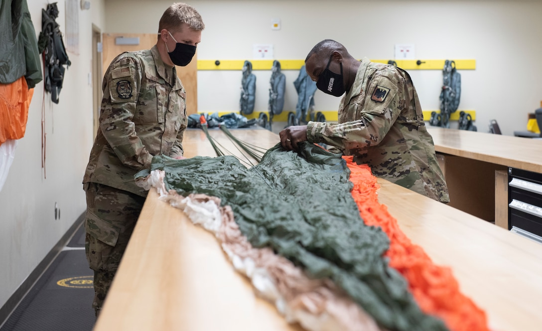 U.S. Air Force Staff Sgt. Wyatt Higgins, left, aircrew flight equipment technician, 120th  Operations Support Squadron and Chief Master Sgt. Maurice Williams, command chief, Air National Guard, perform an annual parachute re-pack inspection at the Montana Air National Guard Base, Great Falls, Montana, Sept. 12, 2021. During his visit, Williams had the opportunity to speak to leaders about the future of the Air National Guard and force development. (U.S. Air National Guard photo by Tech Sgt. Lindsey Soulsby)