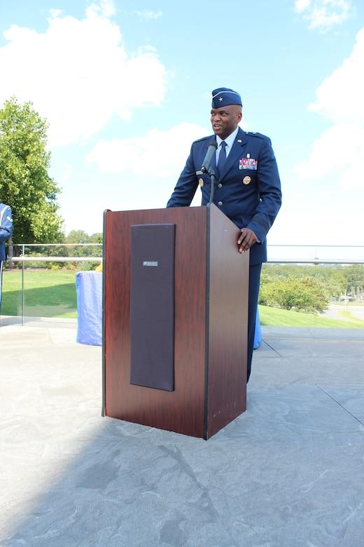 Image of an Airman talking at a podium.