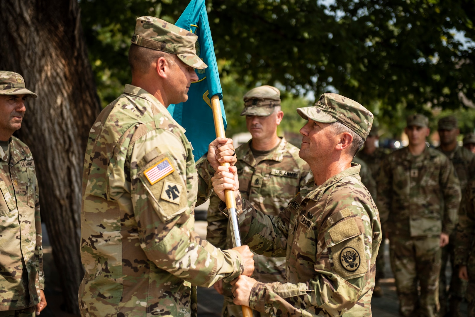 Oklahoma National Guard Lt. Col. Carl Bennett,  outgoing commander with the 63rd CST, passes the unit guidon to Col. Lars Ostervold, commander of the 90th Troop Command, during a change of command ceremony at the Oklahoma City Memorial and Museum, Sept. 1.  The passing of the guidon signifies the formal transfer of authority and responsibility of the unit to the new commander.