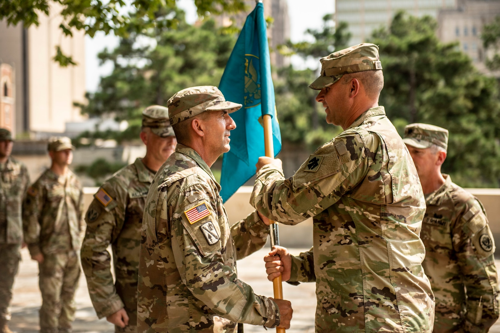 Oklahoma National Guard Maj. Barrett Alexander (left),  incoming commander with the 63rd CST,  receives the unit guidon from Col. Lars Ostervold (right), commander of the 90th Troop Command, during a change of command ceremony at the Oklahoma City Memorial and Museum, Sept. 1.  The passing of the guidon signifies the formal transfer of authority and responsibility of the unit to the new commander.