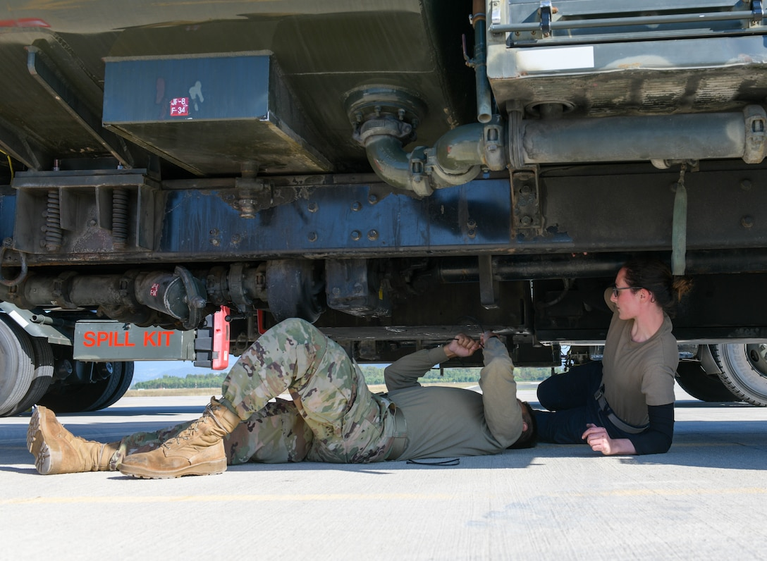 U.S. Air Force Airman 1st Class Sergio Dorado, 31st Civil Engineer Squadron electric power production technician, and Staff Sgt. Emily Scully, 31st Logistics Readiness Squadron fire truck and refueling maintenance technician, close valves on a refueler truck at Cerklje ob Krki Air Base, Slovenia, Sept. 9, 2021. Refueler trucks are used to refuel aircraft and they can carry approximately 6,000 gallons of fuel. (U.S. Air Force photo by Senior Airman Brooke Moeder)
