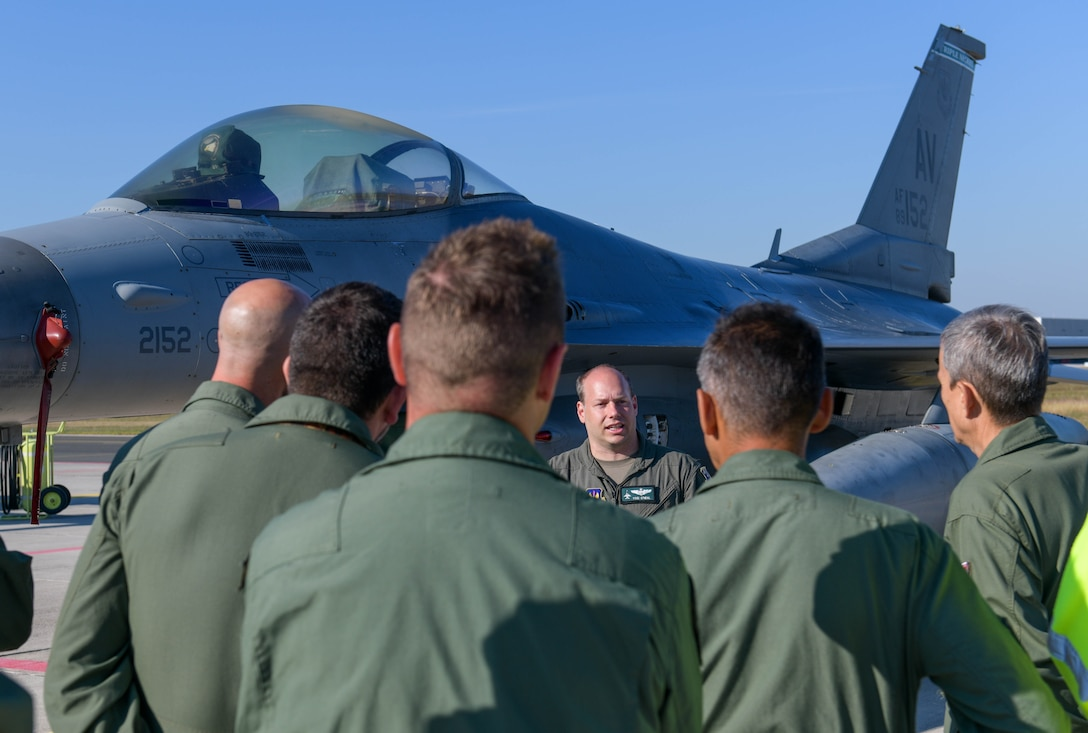 U.S. Air Force Lt. Col. Daniel O'Neil, 555th Fighter Squadron director of operations, briefs Slovenian Armed Forces members about a U.S. Air Force F-16 Fighting Falcon during exercise Agile Wyvern at Cerklje ob Krki Air Base, Slovenia, Sept. 10, 2021. O'Neil briefed the SAF members about the mission and capability of the F-16 and provided general knowledge about the aircraft. (U.S. Air Force photo by Senior Airman Brooke Moeder)