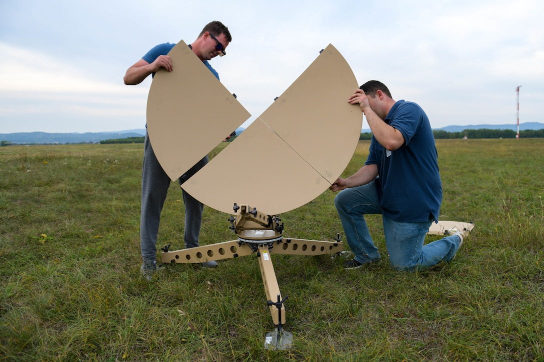 Airman 1st Class Shane Moehle, 31st Communications Squadron radio frequency transition technician, and U.S. Air Force Staff Sgt. Keeling Weber, 31st CS RF transmission supervisor, assemble a Ranger Airbus satellite in preparation for exercise Agile Wyvern at Cerklje ob Krki Air Base, Slovenia, Sept. 7, 2021. The Ranger Airbus allowed for satellite communications and secure messaging capabilities during Agile Wyvern. (U.S. Air Force photo by Senior Airman Brooke Moeder)