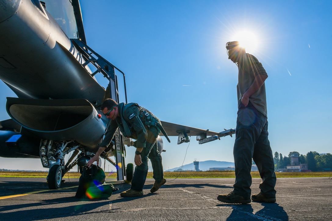 U.S. Air Force 1st Lt. Ryan Kitching, 555th Fighter Squadron F-16 Fighting Falcon pilot, and a U.S. Air Force F-16 crew chief assigned to the 555th Aircraft Maintenance Unit prepare to participate in Agile Wyvern at Cerklje ob Krki Air Base, Slovenia, Sept. 8, 2021. During Agile Wyvern, U.S. and Slovenian Armed Forces conducted Agile Combat Employment training. (U.S. Air Force photo by Senior Airman Brooke Moeder)
