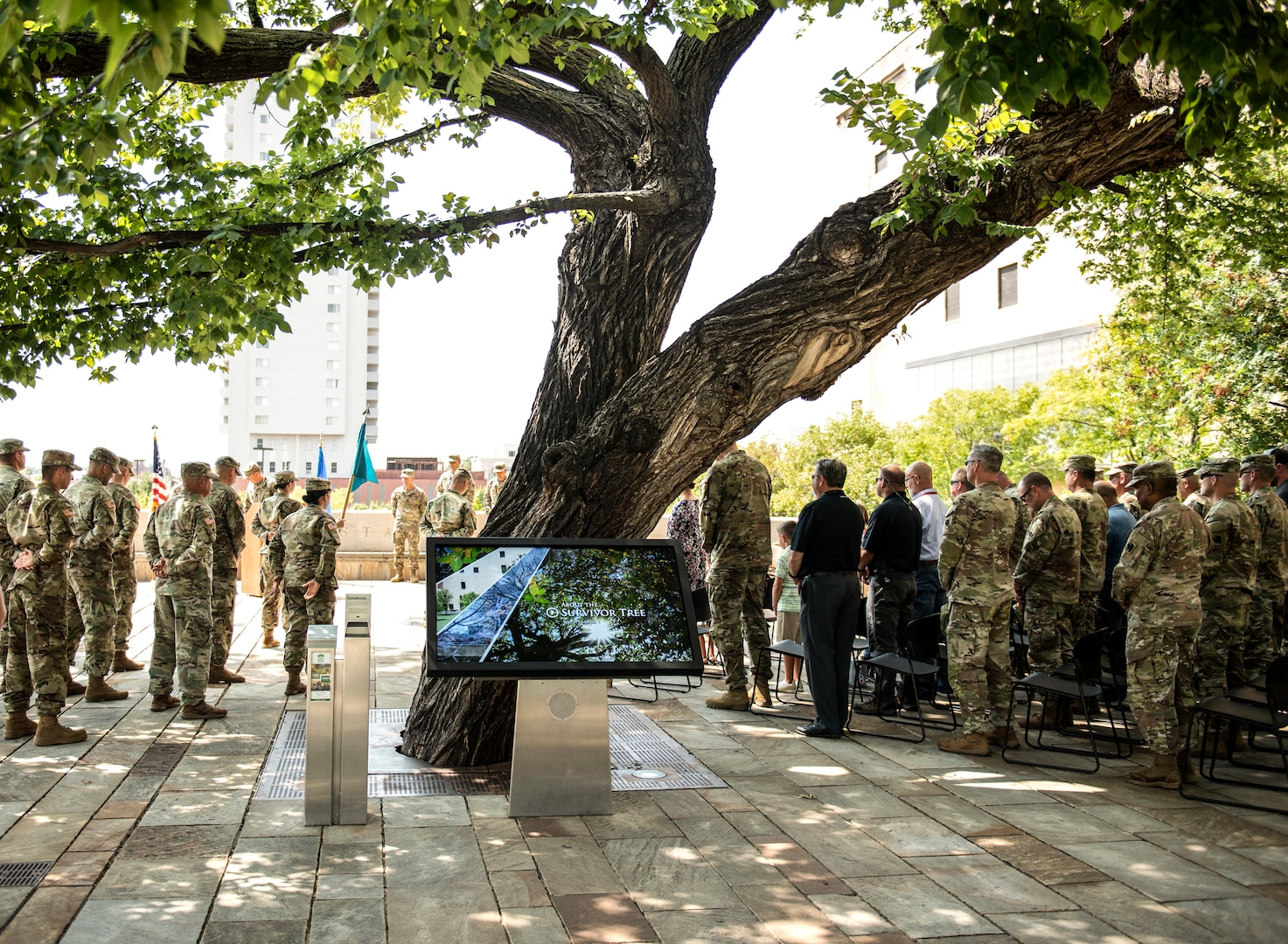 Members of the Oklahoma National Guard, community partners and family members gather around the Murrah Bombing Survivor Tree during a change of command ceremony at the Oklahoma City National Memorial and Museum in Oklahoma City, Sept. 1, 2021.  The 63rd CST is designed to provide a specialized response to chemical, biological, radiological or nuclear incidents at the authorization and direction of the Governor.