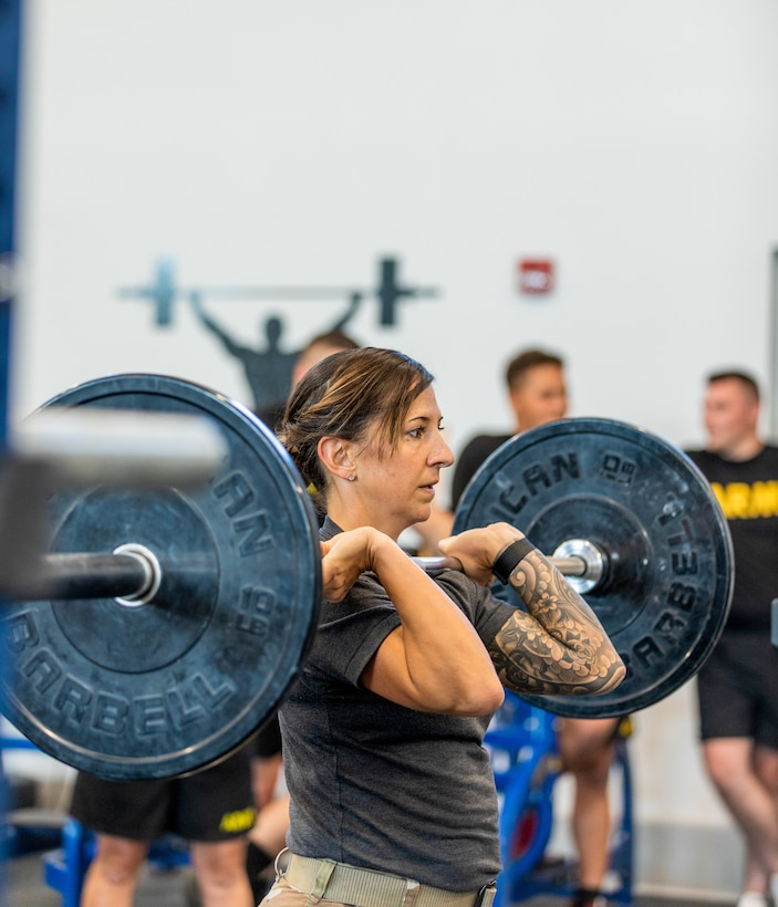 Master Sgt.  Kristen Roles with the Kentucky Air National Guard 123rd Maintenance Squadron prepares to attempt an overhead press as part of an exercise drill at Boone National Guard Center on Sept. 7th, 2021. As part of the AXE Camp's cadre team, her role is to instruct students on proper physical exercise techniques and holistic health strategies.