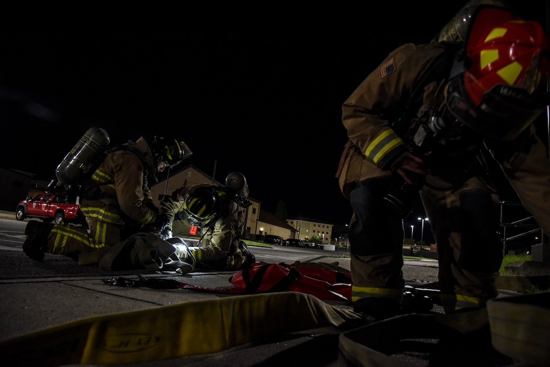 Firefighters from the 51st Civil Engineer Squadron arrange equipment during a training event