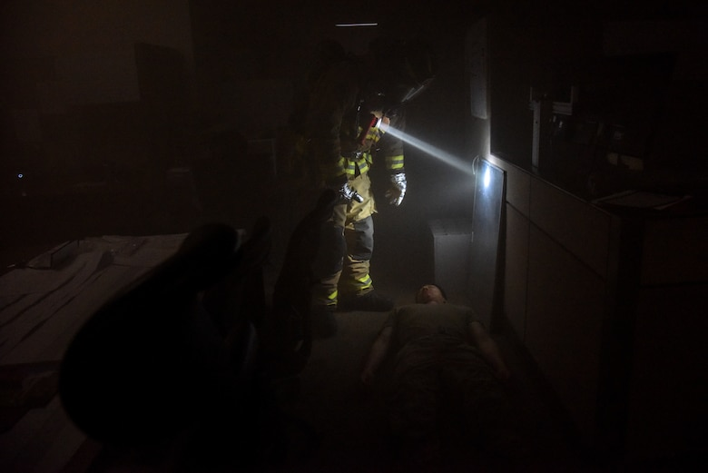 A firefighter from the 51st Civil Engineer Squadron discovers a wounded Airman during a training scenario