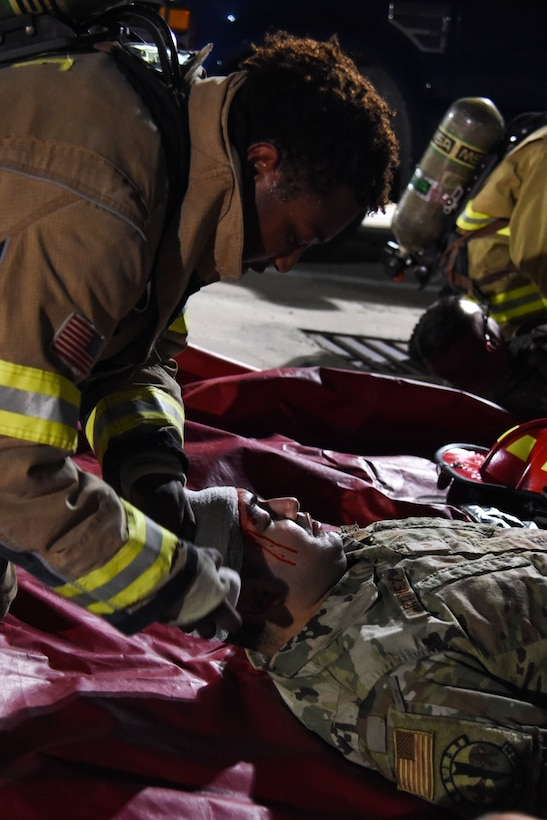 Staff Sgt. Tyler McFarland, 51st Civil Engineer Squadron firefighter, provides first aide to a wounded Airman during a training event