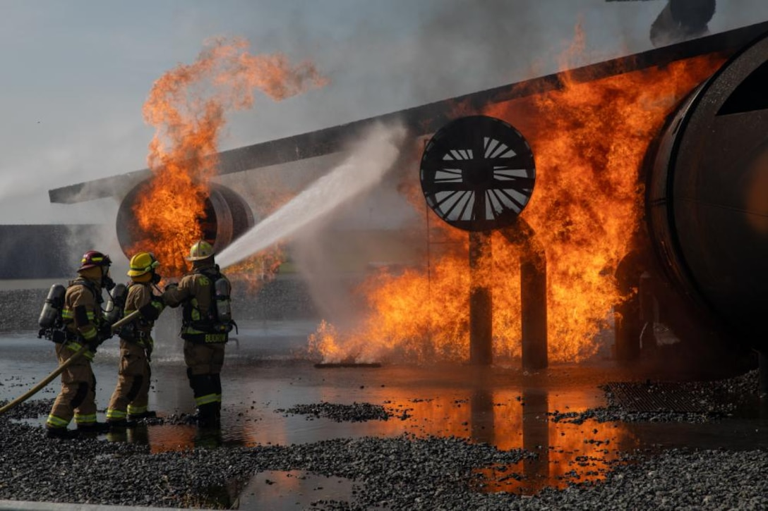 Station fire department members spray a burning aircraft simulation during a live-fire drill as part of an airport rescue firefighter course at Marine Corps Air Station Iwakuni, Japan, on Sept. 10, 2021. The course is designed to train and enable the air station's fire department to support Aircraft Rescue Fire Fighting Marines in responding to potential aircraft fires.