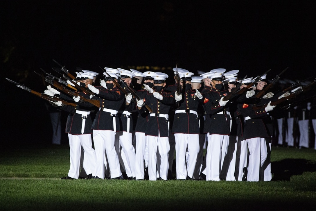 """Marines with the Silent Drill Platoon perform their """"bursting bomb"""" sequence during the Friday Evening Parade at Marine Barracks Washington, June 4, 2021. The guest of honor for the evening was The Honorable Michèle A. Flournoy, 9th Undersecretary of Defense for Policy, and the hosting official for the evening was Lt. Gen. Charles G. Chiarotti, Deputy Commandant for Installations and Logistics."""