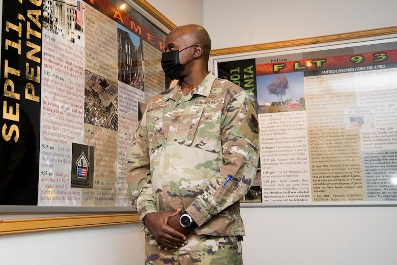 Man in uniform stands next to display.