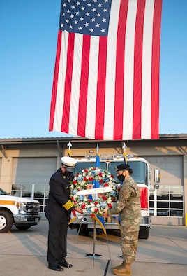 Jacob King, 788th Civil Engineer Squadron fire chief, and Lt. Col. Nicole Schatz, 88th Security Forces Squadron commander, place a wreath in front of Fire Station One during commemoration of the 20th anniversary of the 9/11 attacks Sept. 10, 2021, at Wright-Patterson Air Force Base, Ohio. King and Schatz symbolized the firefighters and police officers who died in the attack. (U.S. Air Force photo by R.J. Oriez)