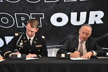 two men sitting at a table, one in a suit and the other in an Army uniform, signing a piece of paper.