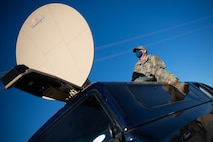 U.S. Air Force Tech. Sgt. Gerald Hawk, the 354th Contracting Squadron tactical communication noncommissioned officer in charge, sets up communication equipment during a Capabilities-Based Assessment at the Yukon Training Area, Sept. 14, 2021.