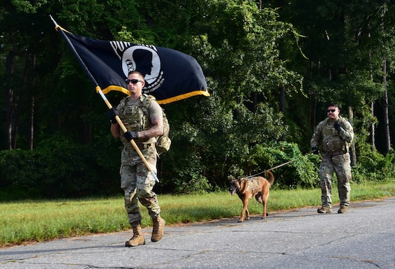 Tech. Sgt. Kyle Shy, left, 4th Security Forces Squadron military working dog kennel master, MWD Eenoch, and Staff Sgt. Jesus Amaya, 4th SFS MWD handler, walk in a unit ruck march at Seymour Johnson Air Force Base.