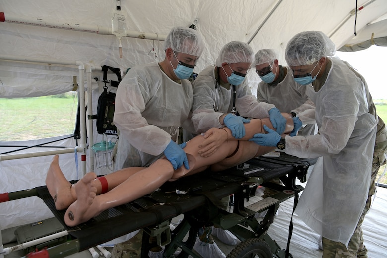 U.S. Air Force medics with the 156th Medical Group Detachment 1, Chemical, Biological, Radiological, Nuclear and high-yield Explosive Enhanced Response Force Package, evaluate and treat a simulated victim during a search and extraction training exercise at Camp Santiago Joint Training Center, Salinas, Puerto Rico, Aug. 19, 2021.