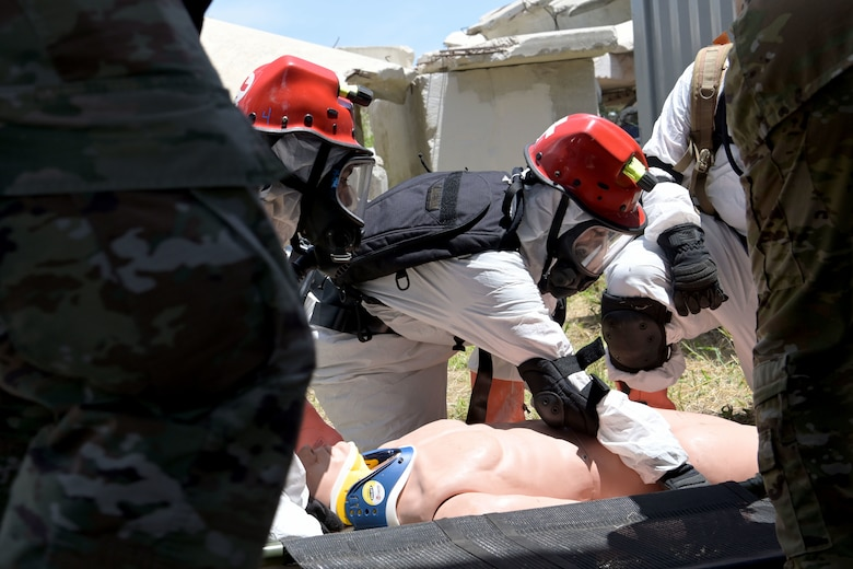 U.S. Airmen with the 156th Medical Group Detachment 1, Chemical, Biological, Radiological, Nuclear and high-yield Explosive Enhanced Response Force Package, assess, stabilize and prepare to transport a simulated victim during a search and extraction training exercise at Camp Santiago Joint Training Center, Salinas, Puerto Rico, Aug. 19, 2021.