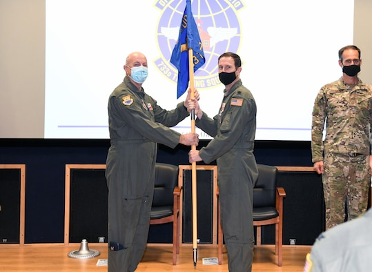 """Col. James """"JC"""" Miller, 433rd Operations Group commander, passes the 733rd Training Squadron's guidon to Lt. Col. Steven Radtke signifying his accepting command of the unit Sept. 10, 2021 at Joint Base San Antonio-Lackland, Texas. Previous to this assignment, Radtke was the 356th Training Squadron commander here. (U.S. Air Force photo by Master Sgt. Kristian Carter)"""