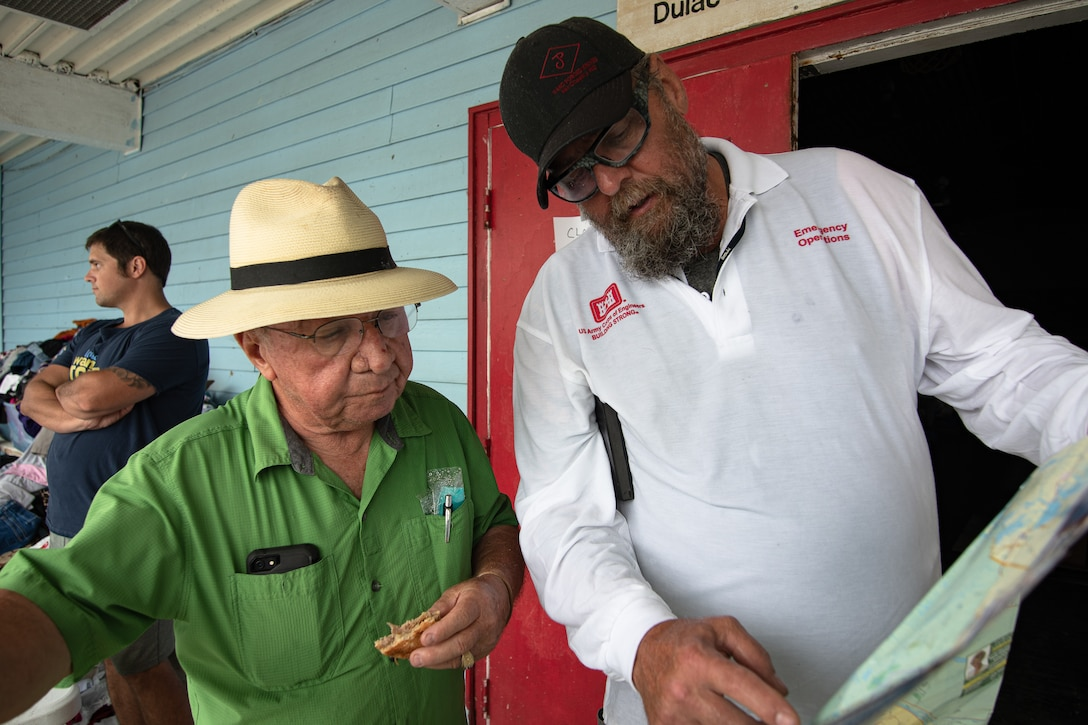James Muilenburg, a US Army Corps of Engineers, Omaha District employee serving as a national local government liaison, looks over a map with Rev. Kirby Verret, a pastor and the Coordinator of Indian Education at Terrebonne Parish School Board as they discuss the highly impacted areas that Muilenburg should visit.