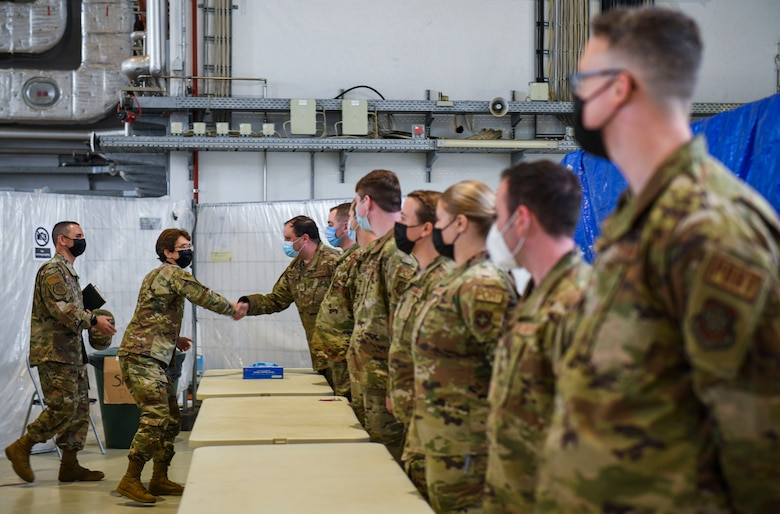 General shakes hands with Airmen.