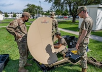 Uniformed people assemble a collapsible satellite dish.