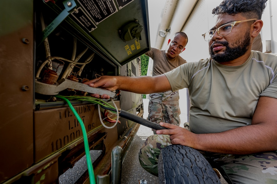 A man in uniform uses a wrench-like tool to connect large wires to a piece of machinery.