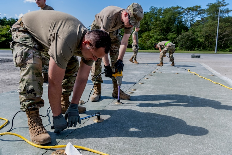 People in uniform use power tools to attach a surface to the ground.