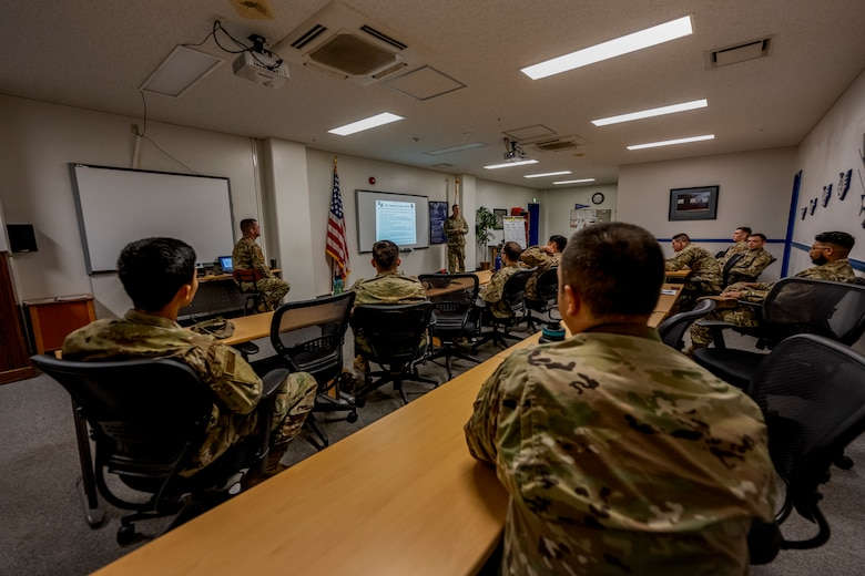 Several people in uniform sit in a classroom.