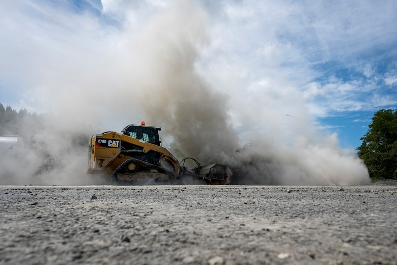 A piece of heavy machinery kicks up a cloud of dust.