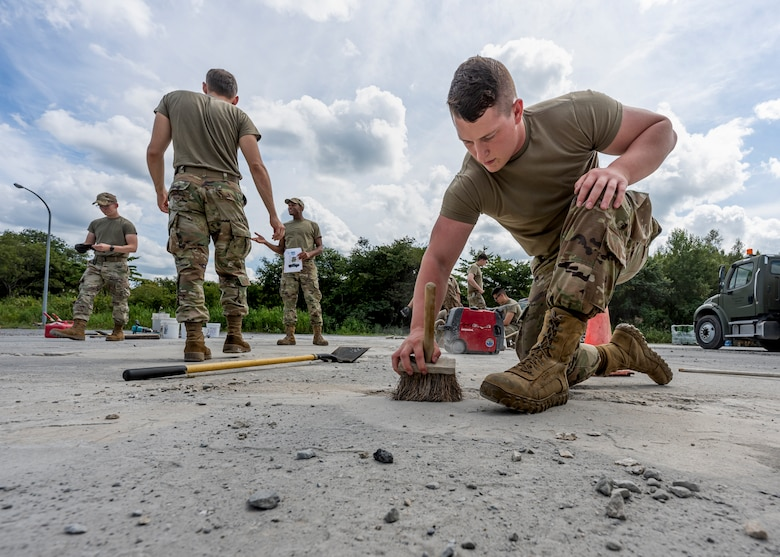 A man in uniform uses a brush to clean out a divot in concrete.