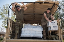 Oklahoma National Guard Spcs. Michael West, left, and Gage Stone, truck drivers with Alpha Company, 120th Engineer Battalion, 90th Troop Command, distribute water, ice and food to those affected by Hurricane Ida in LaPlace, Louisiana, Sept. 7, 2021. Oklahoma National Guardsmen drove throughout neighborhoods to distribute supplies directly to residents.