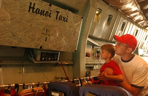A man and child looking at the wall of signatures aboard the C-141 Starlifter known as the Hanoi Taxi
