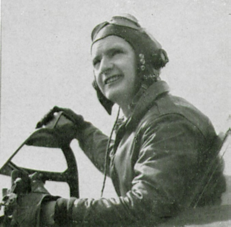 """Flight Officer (F/O) William (NMI) Gorman, T-223063, poses for a picture in the cockpit of a Republic P-47D Thunderbolt fighter. Note his right hand rests atop the rear-view mirror on the windscreen of this """"Razorback"""" version of the P-47.  (The Story of the 371st Fighter Group in the ETO)"""