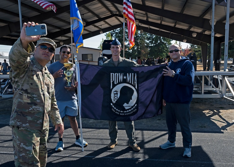 U.S. Air Force Chief Master Sgt. Joseph Arce, 62nd Airlift Wing command chief, takes a photo with 4th Airlift Squadron Airmen after receiving the award for most miles ran by a team during the 24-hour POW/MIA Remembrance Run at Joint Base Lewis-McChord, Washington, Sept. 16, 2021. Airmen with the 4th AS ran 234 miles in total; paying their respects to the memory of those Americans who were prisoners of war or were, and may still be, missing in action. (U.S. Air Force photo by Senior Airman Zoe Thacker)