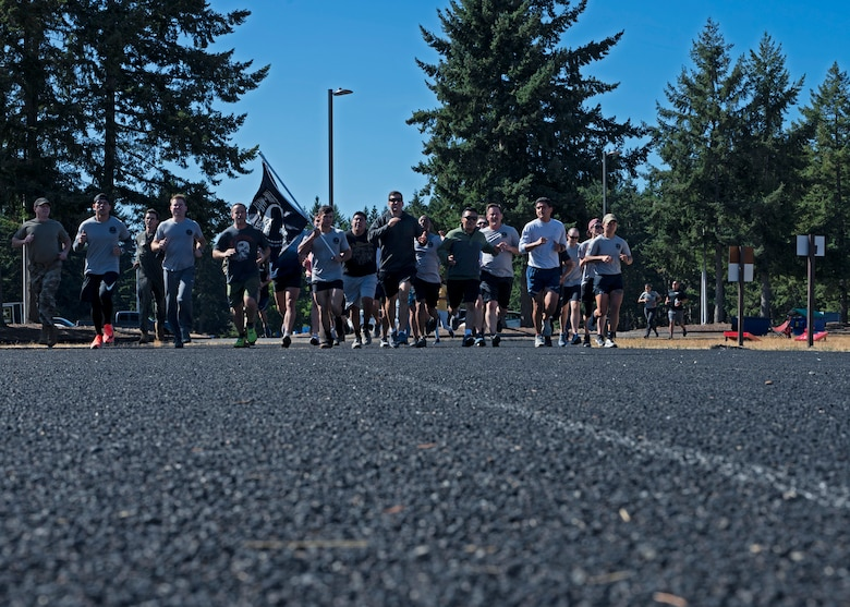 U.S. Airmen with Team McChord complete their final lap of the 24-hour POW/MIA Remembrance Run at Joint Base Lewis-McChord, Washington, Sept. 16, 2021. Collectively, Team McChord ran more than 300 miles to honor the sacrifice and memory of those Americans who were prisoners of war or were, and may still be, missing in action. (U.S. Air Force photo by Senior Airman Zoe Thacker)