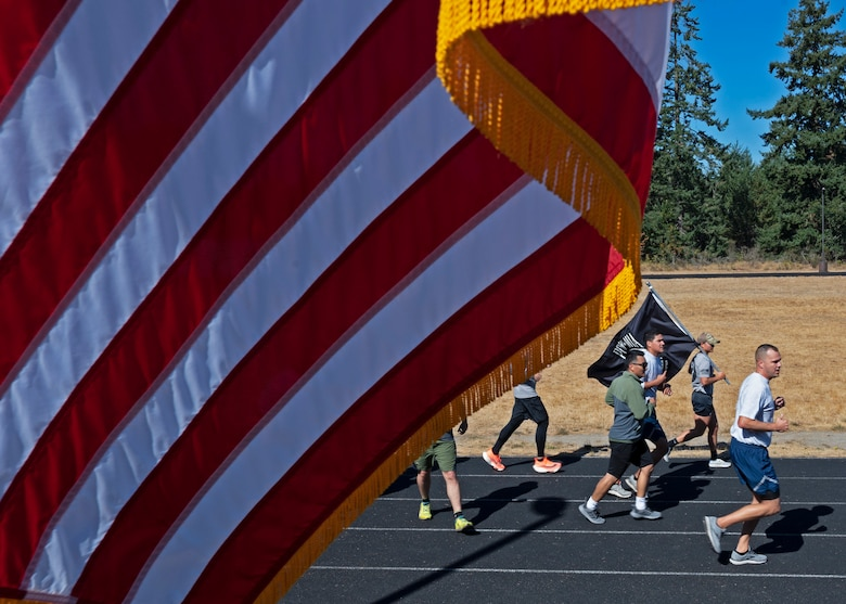 U.S. Airmen with the 627th Civil Engineer Squadron run with the POW/MIA flag during the 24-hour remembrance run at Joint Base Lewis-McChord, Washington, Sept. 16, 2021. Collectively, Team McChord ran more than 300 miles to honor the sacrifice and memory of those Americans who were prisoners of war or were, and may still be, missing in action. (U.S. Air Force photo by Senior Airman Zoe Thacker)