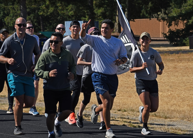U.S. Airmen with the 627th Civil Engineer Squadron run their final lap with the POW/MIA flag during the 24-hour remembrance run at Joint Base Lewis-McChord, Washington, Sept. 16, 2021. Collectively, Team McChord ran more than 300 miles to honor the sacrifice and memory of those Americans who were prisoners of war or were, and may still be, missing in action. (U.S. Air Force photo by Senior Airman Zoe Thacker)